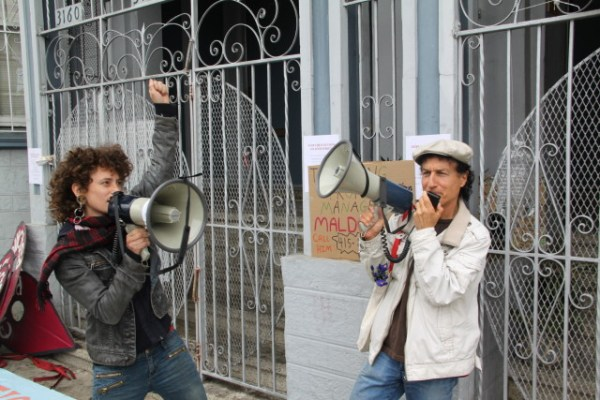 """Erin McElroy, of the Anti-Eviction Mapping Project, and Tommi Avicolli Mecca, of the Housing Rights Committee, energized the crowd with chants of """"Hell no, we won't go!"""" and """"What do we want? Stop the evictions! When do we want it? Now!"""" Photo by Joe Rivano Barros."""