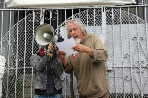 Tenant Tom Anderson read aloud a letter to landlord Aquilina, asking him to talk to the tenants and set the record straight. Photo by Joe Rivano Barros.