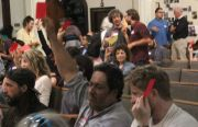 The crowd at a Plaza 16 meeting shows their support for a campaign against Maximus Development by holding up red cards. Photo by Daniel Hirsch.  August, 2014