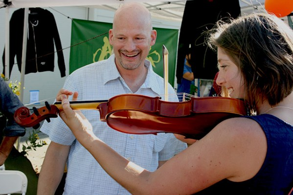 Ben Hippen helps a volunteer try out a violin at the Community Music Center's instrument petting zoo, with an assortment of string and percussion instruments available to try out. Photo by Laura Wenus