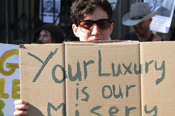"""Your luxury is our misery,"" read the sign held up by one of the protesters at the march. Photo by Andrea Valencia"
