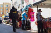 A security guard walks through Arriba Juntos flea market in April.