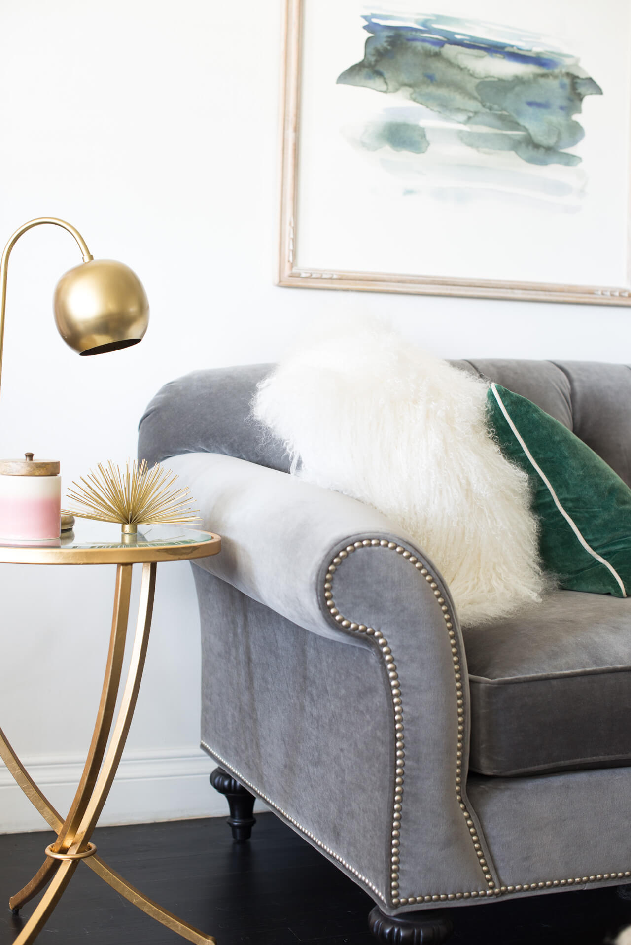 brass table lamp with gray tufted couch
