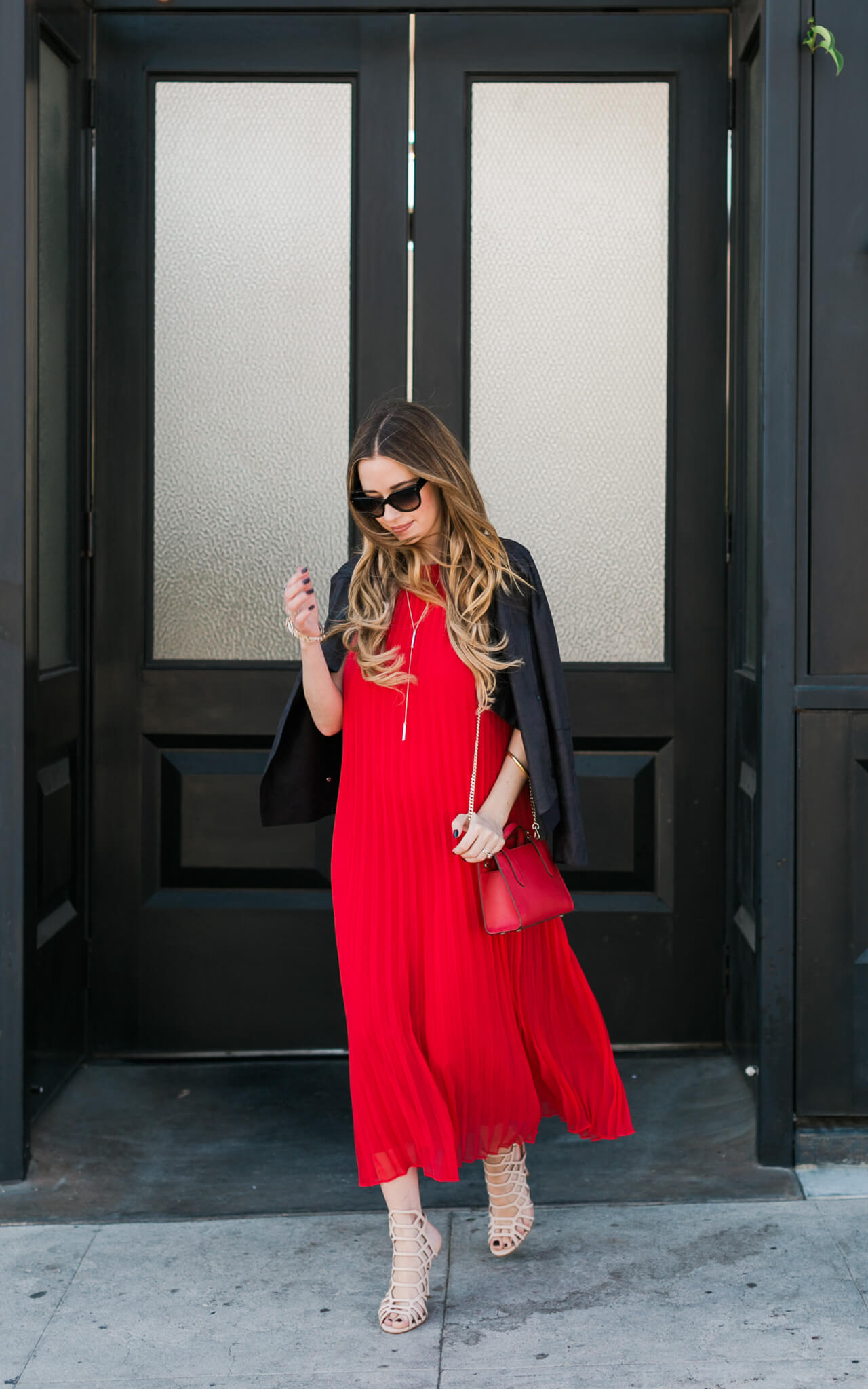 a pretty red pleated dress with nude sandal heels and a leather jacket