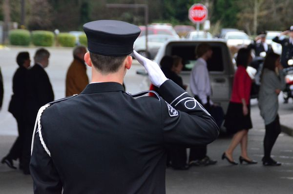 The honor guard of Don Navarre's brother and sister firefighters stand at attention as the family follows the casket bearing his body into Westgate Chapel.