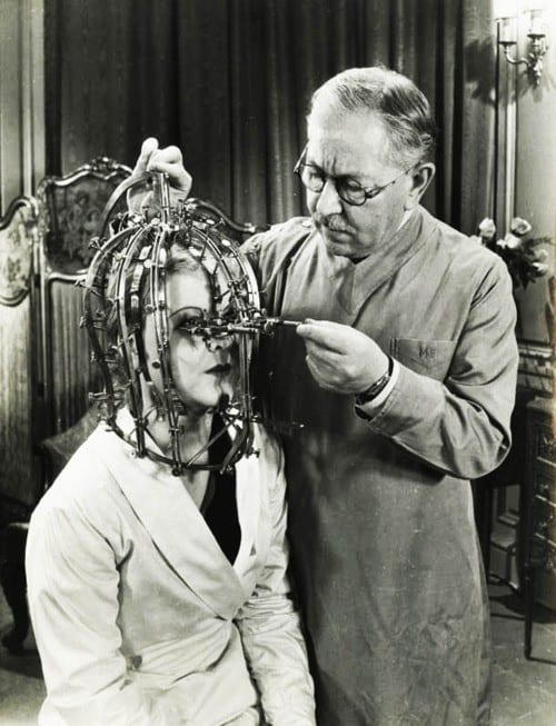 "1934 Max Factor demonstrates his ""scientific device"" the Beauty Micrometer which detects defects in feminine beauty that are imperceptible to the naked eye. Image courtesy of FilmMakerIQ.com"
