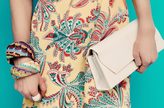 Lady in stylish summer dress and stylish accessories. Bracelets and clutch