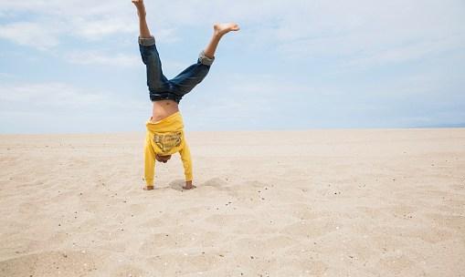 Boy doing handstand on beach