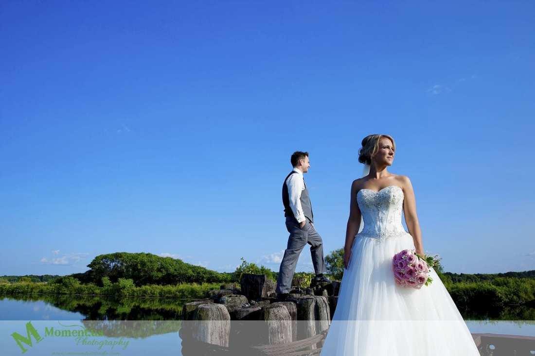 Elegant Cornwall wedding - groom standing on canal posts