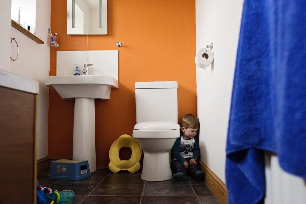 boy hiding next to toiletduring session with Wales family photographer