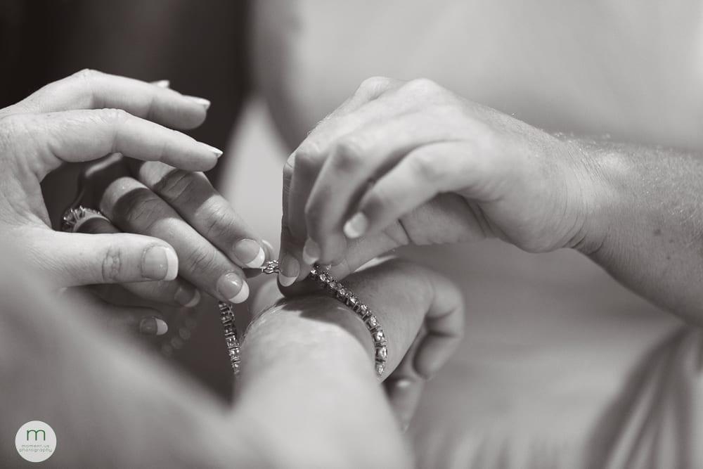 bride helping bride with bracelet