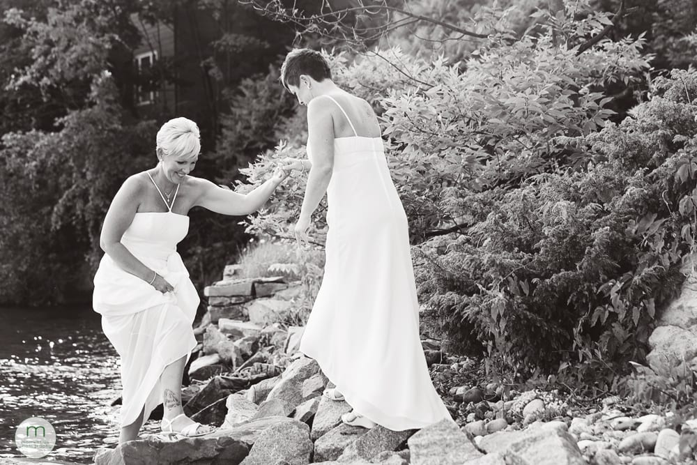 2 brides by river on rocks