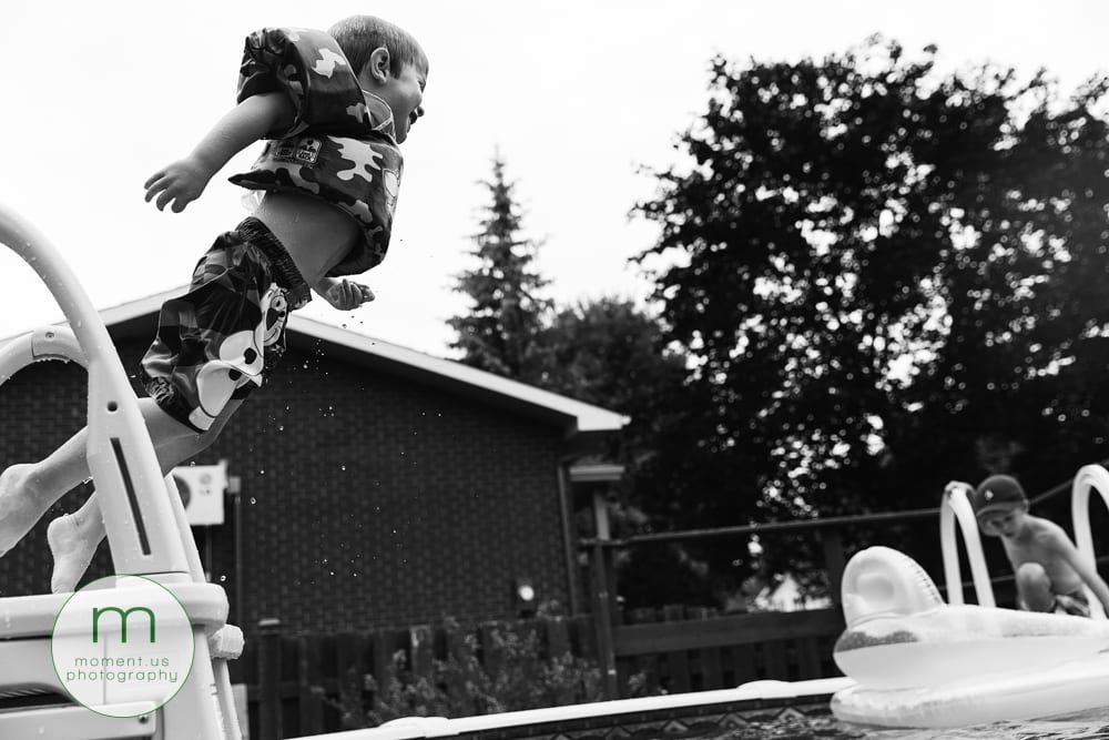 boy leaping into pool