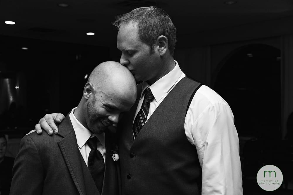 groom kissing friend's head