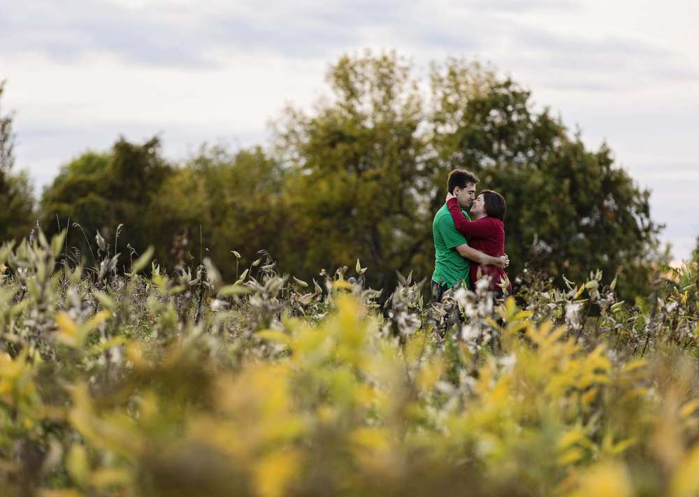 Ontario wedding photographer - couple cuddling for Cornwall engagement photos in abandoned field