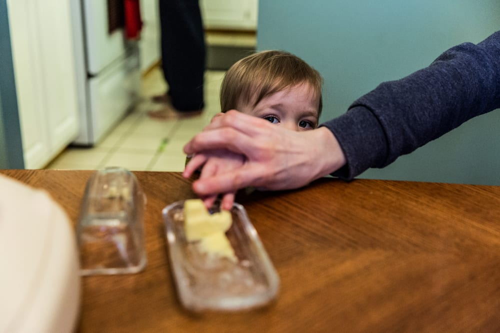 Cornwall family photography - girl caught with finger in butter