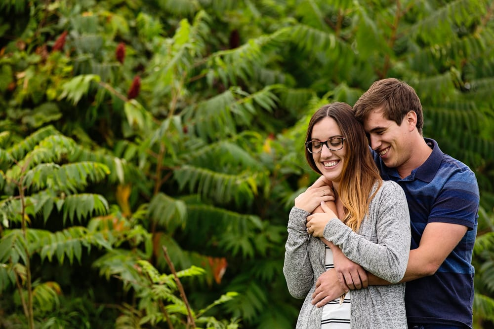 Ontario wedding photographer - couple cuddling for Cornwall engagement photos in front of sumac