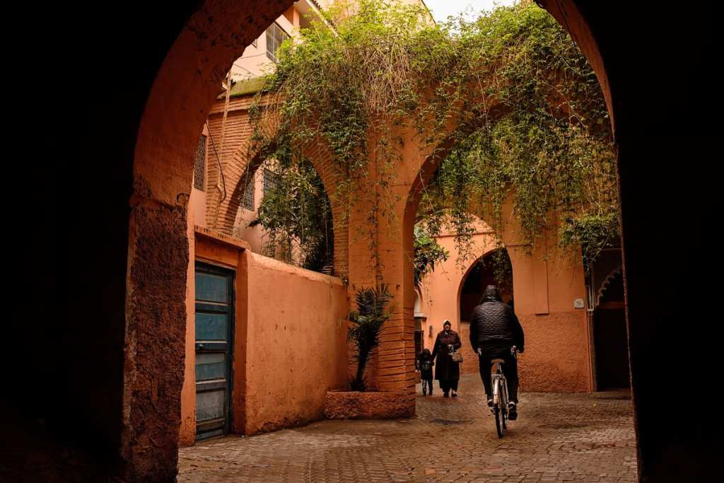 Wedding photographer in Morocco - cyclist and woman with child under archway