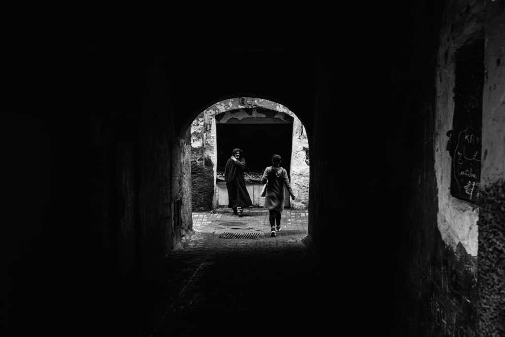 Wedding photographer in Morocco - man and woman pass under archway