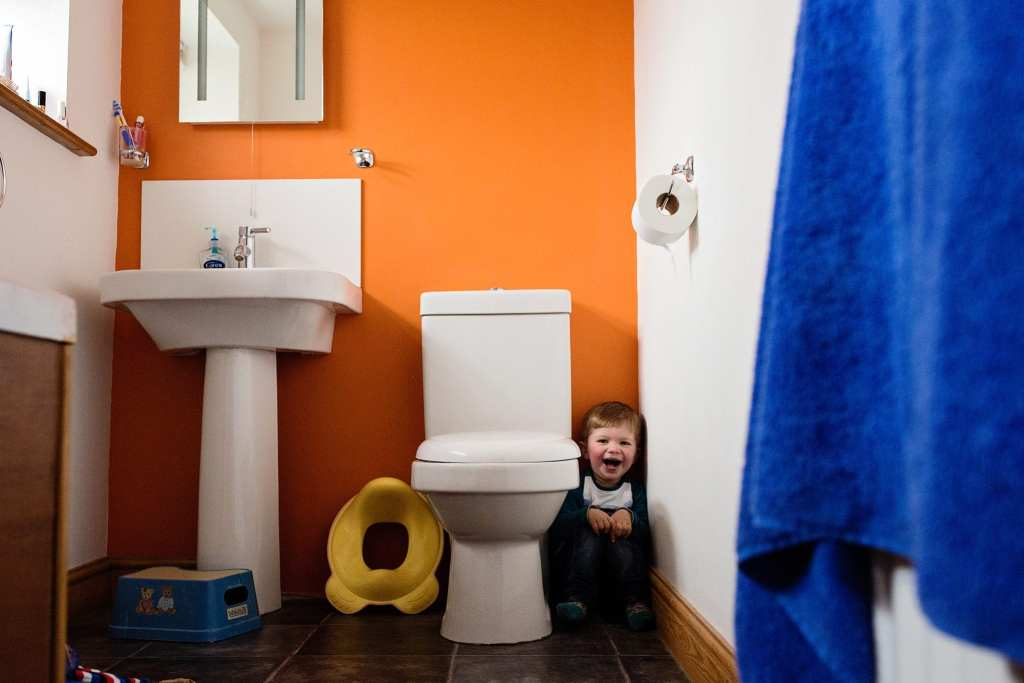 boy hiding next to toilet during session with South Wales family photographer