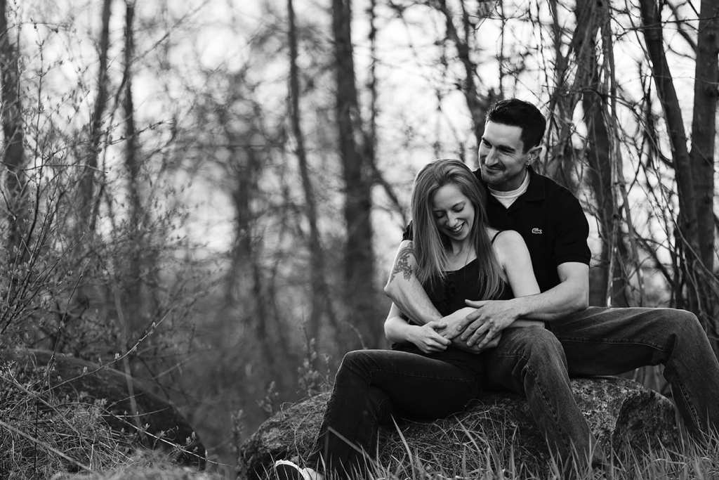 laughing while sitting on a rock during Cornwall engagement session