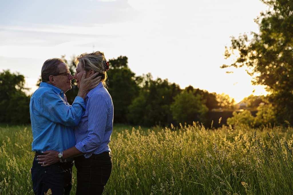 Man holding fiancee's face in field