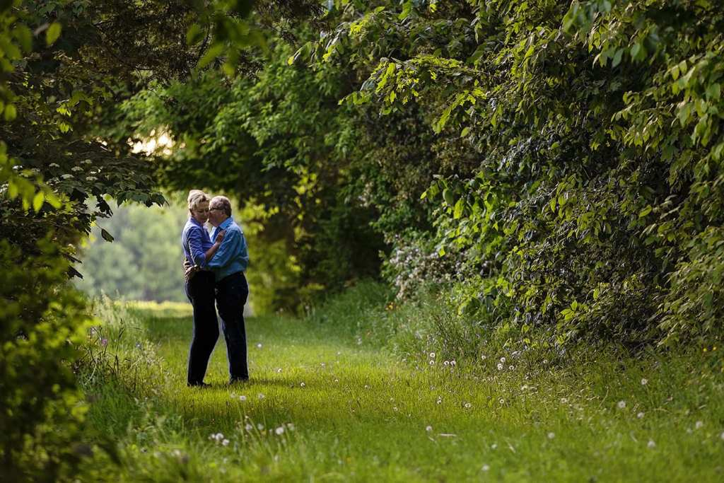 Couple hugging in tree tunnel
