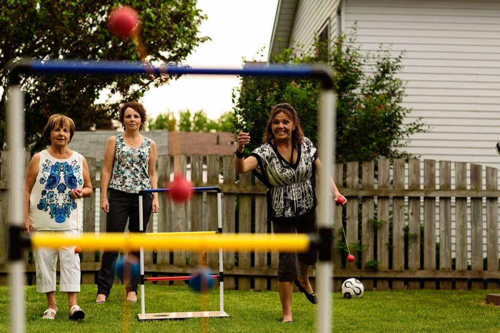 women playing backyard summer yard games during candid cornwall family photography session