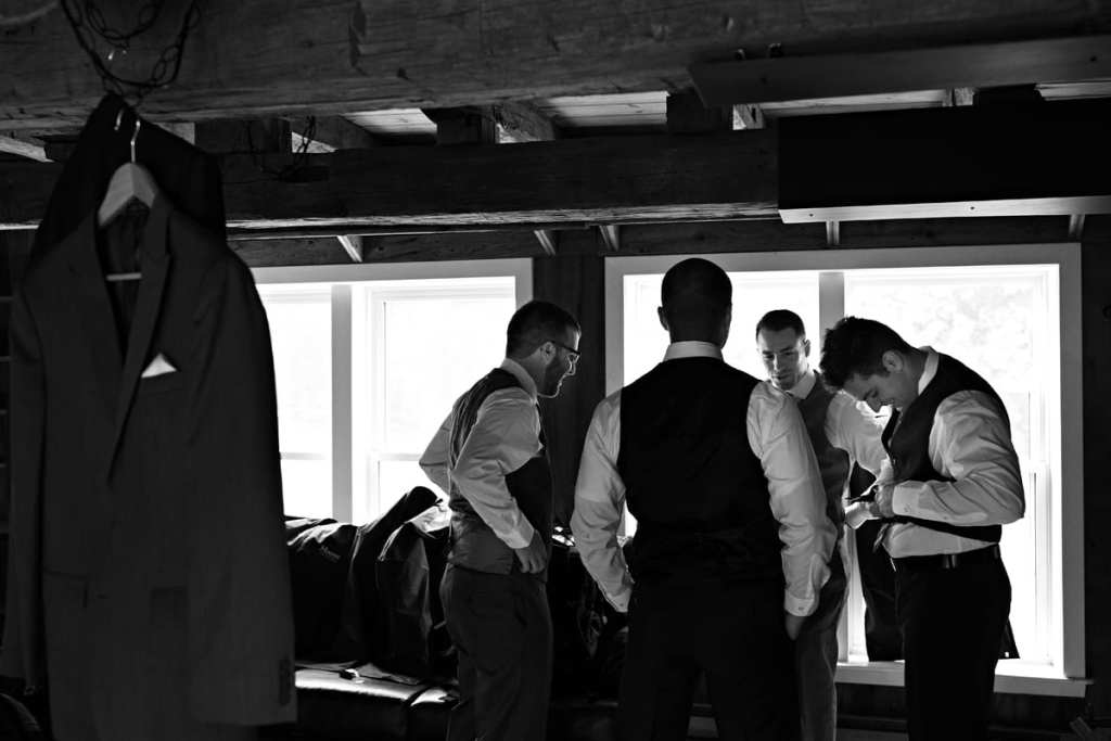 Groom and wedding party getting ready in rustic log beam room