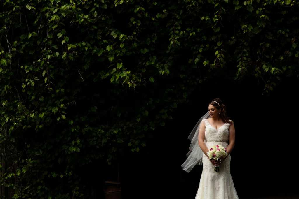 Bride in lace mermaid gown with bouquet in front of lush greenery