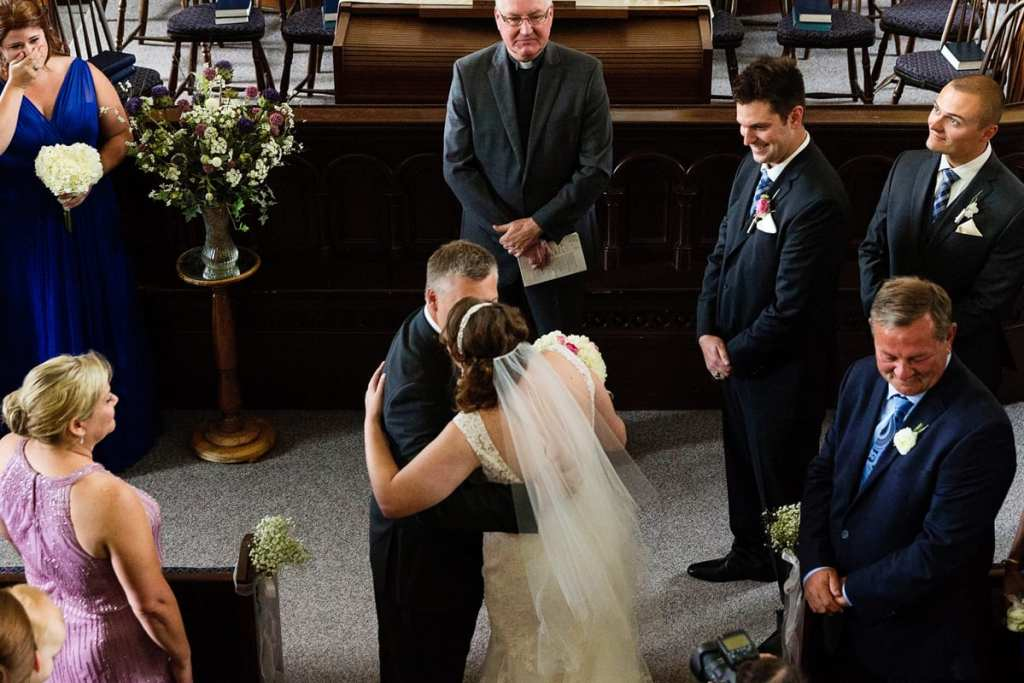 Father of the bride giving away daughter at the altar