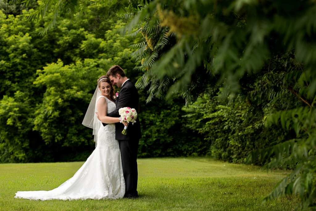 Bride holding bouquet and groom with arms around her waist in lush greenspace