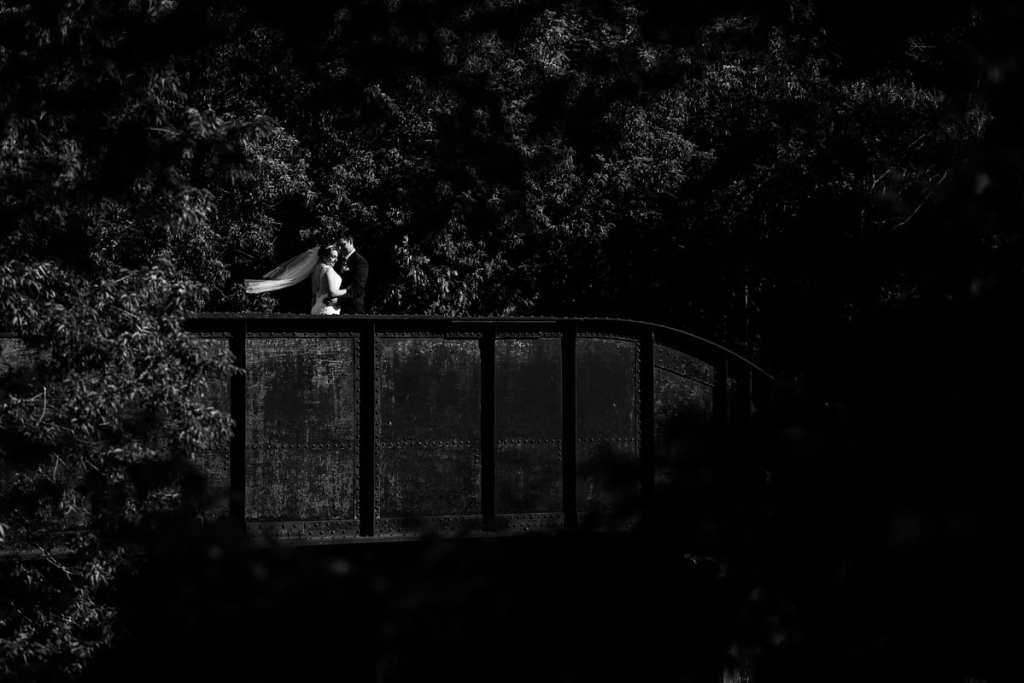Dramatic photography of bride and groom on country bridge