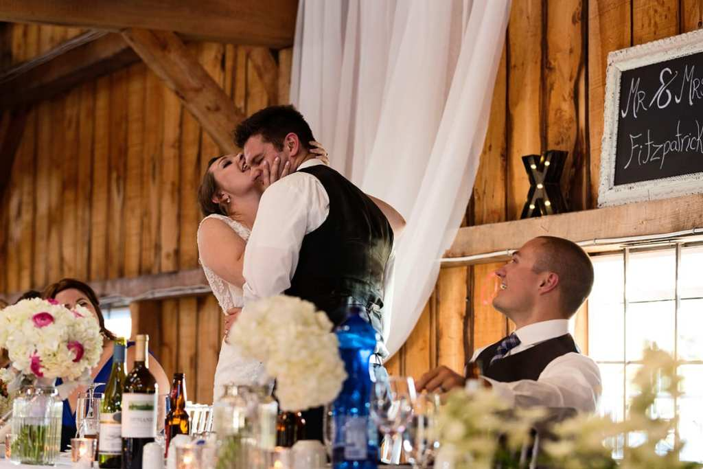 Bride licking groom's face at head table in Williamstown Fairgrounds wedding