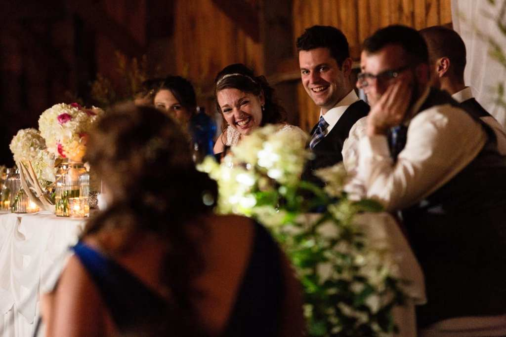Bride and groom laughing with wedding party at head table