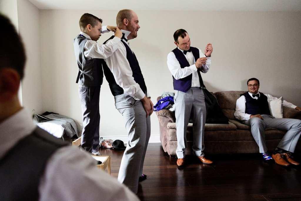 Ring bearer helping groomsmen during prep