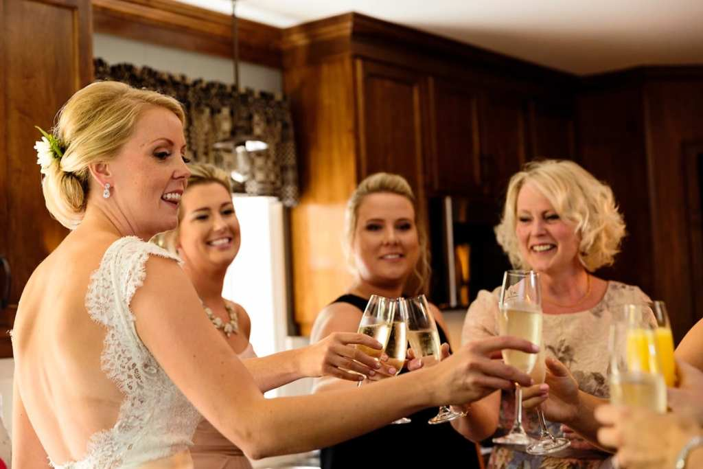 bride and attendants toasting with champagne in family kitchen