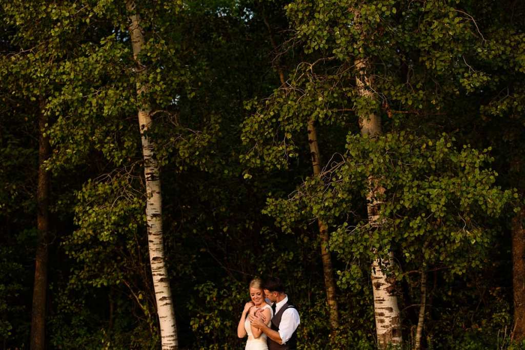 Groom holding bride in poplar tree stand at sunset