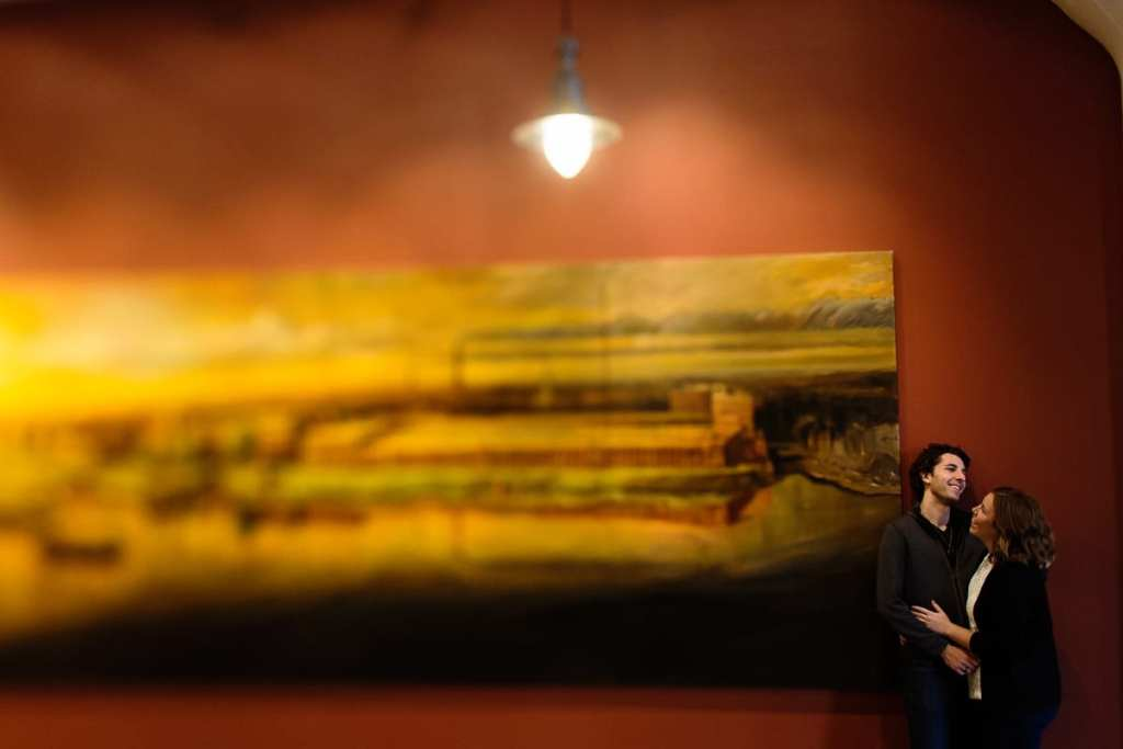 Engagement photo of smiling couple with gallery painting and industrial light