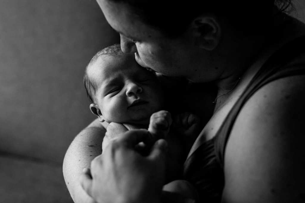Closeup of mom caressing newborn son