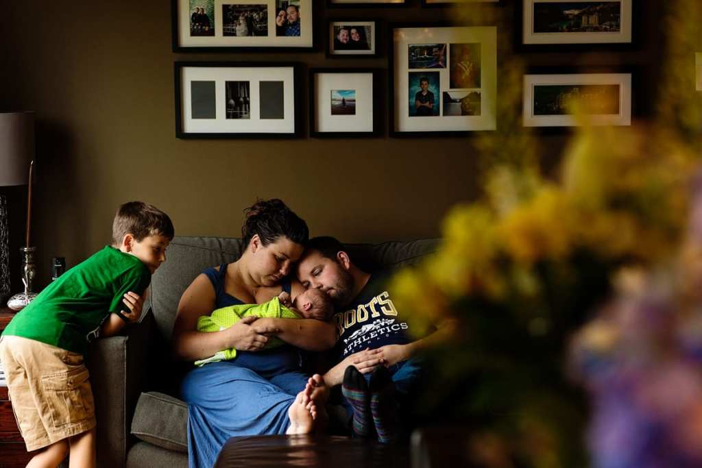 Candid family shot of boy meeting baby brother on living room couch