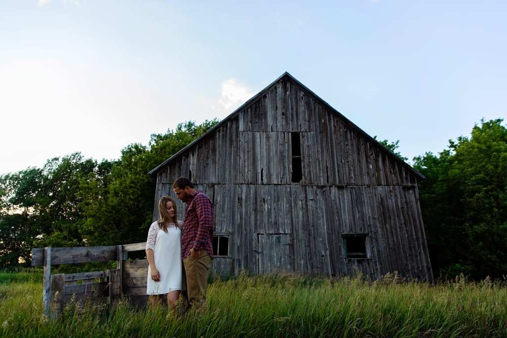 Rural Ontario engagement session in tall grass with barn
