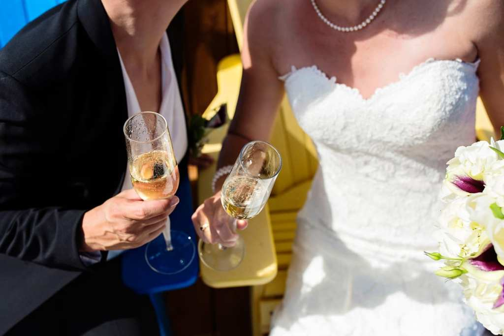 brides celebrating with champagne glasses on adirondack chairs in Cornwall summer wedding