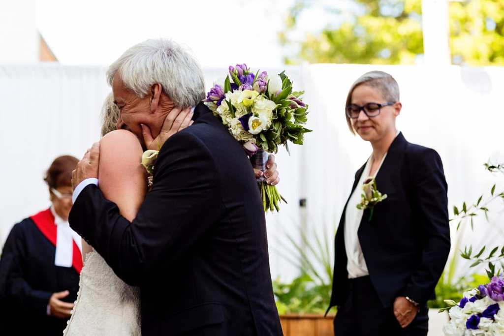 bride and father hugging at alter during wedding ceremony in chic cornwall wedding