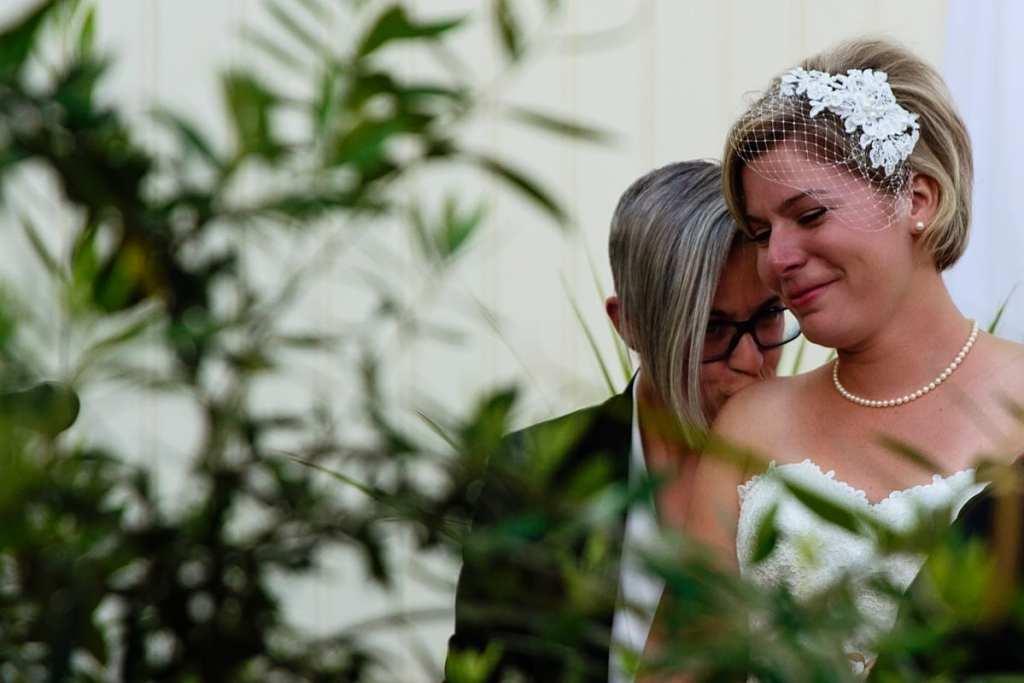 bride kissing bride's shoulder in chic LGBTQ Cornwall wedding