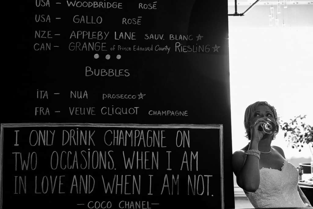 bride wearing fascinator with champagne quote on wall