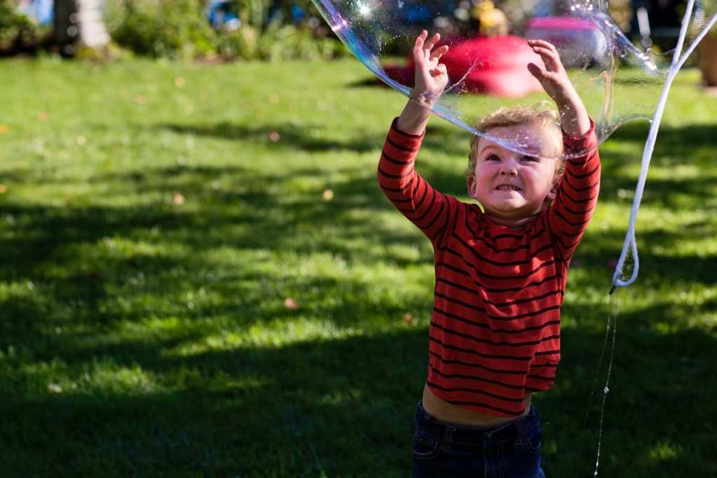 little boy making funny face while popping large soap bubbles