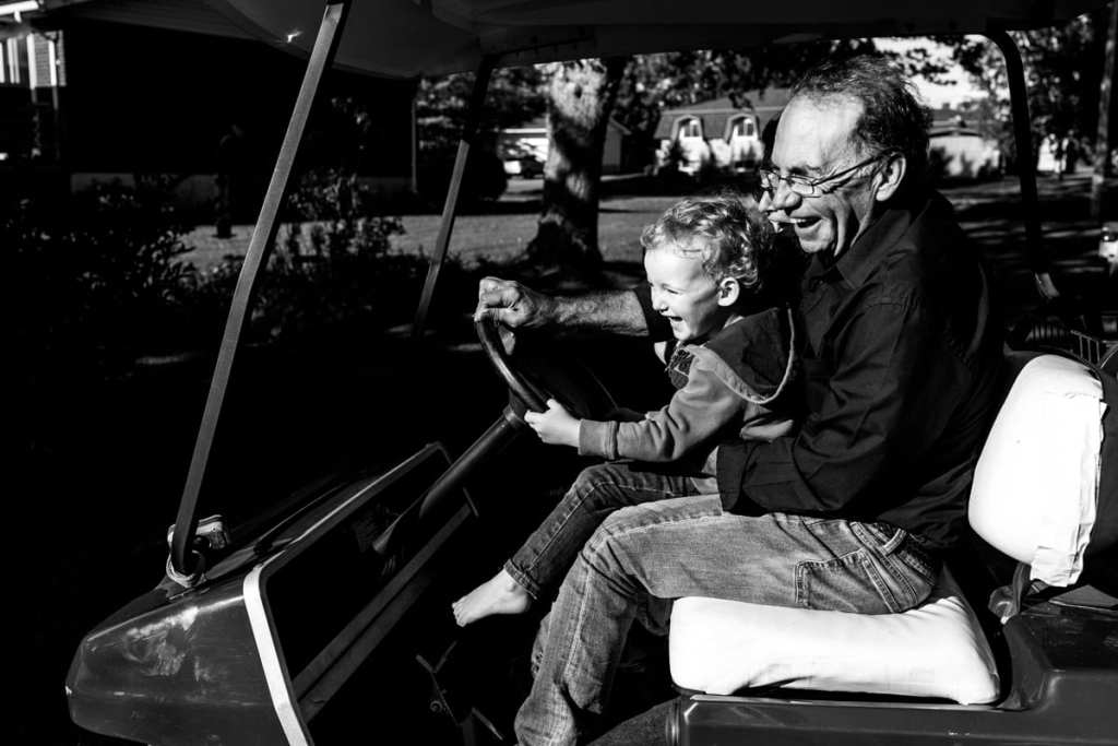 grandpa and little boy laughing while driving golf cart during candid Cornwall backyard family session