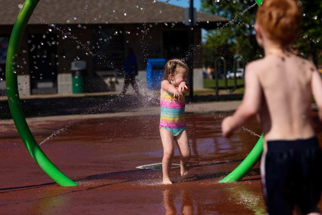 brother spraying sister with water at splash park