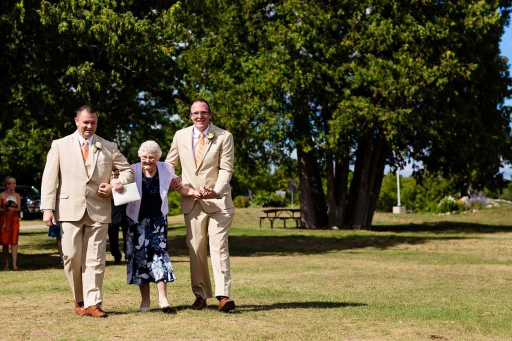 groom and best man helping grandmother to wedding ceremony